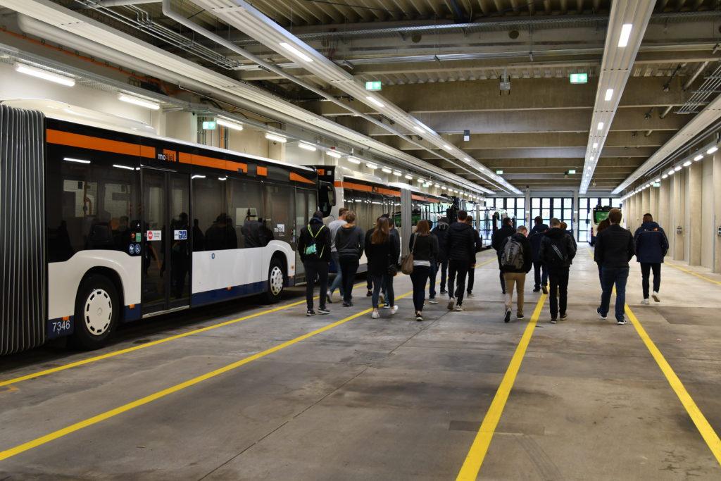 Azubis laufen durch ein Bus-Depot